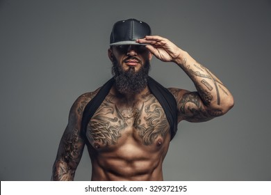 Brutal tattooed man in black cap posing in studio. Isolated on grey background.