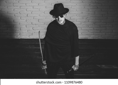 brutal tattooed man with a sword. Warrior in black sunglasses, hat and clothes, top view. Man with swords standing on wooden floor. Honor and dignity. Samurai, buddhist concept. Harakiri, suicide