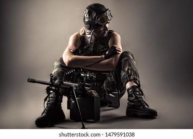 brutal woman sitting on floor with machine gun