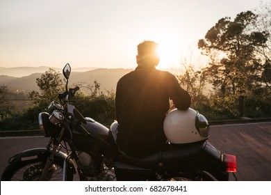 Brutal young biker wears black t-shirt and jeans, sits on his black old motorbike, holds white helmet and looks on beautiful soft sunset on parking with panorama view on natural mountains.