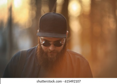 8502bf6b190 A brutal young man with a huge beard in sunglasses and a cap in the woods