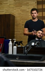 a brutal-looking Barber cuts the hair of an Indian guy. cinematic image