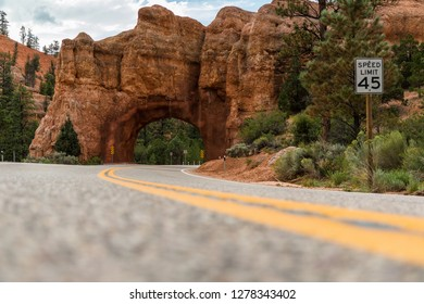 BRYCE CANYON NATIONAL PARK - 22 AUG 2018: Road driving through tunnel arch at Red Rock State Park near Bryce Canyon National Park with a close-up of a road sign