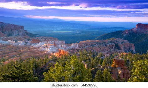 Bryce Canyon National Park sunrise. Dramatic clouds illuminating the rock formations and hoodoos amidst forest land.