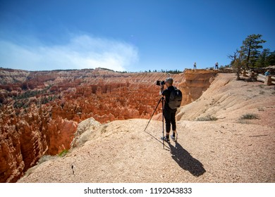 BRYCE CANYON, UTAH - September 8, 2018: Smoke from a wildfire rises over Bryce Canyon as park visitors ignore warning signs and fences, engaging in dangerous activities in search of the perfect photo.