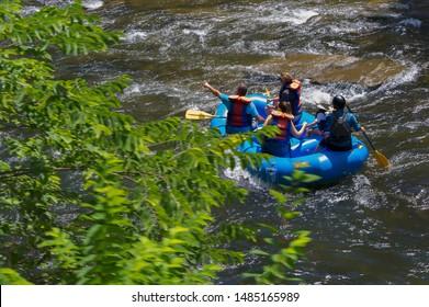 Bryson, North Carolina, USA - August 3, 2019:  Seen from a moving train people enjoying rafting down the Nantahala River in the Nantahala National Forest