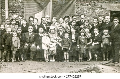 BRZESKO NOWE, POLAND, CIRCA FORTIES - Vintage photo of big multigenerational family with children posing during a wedding party