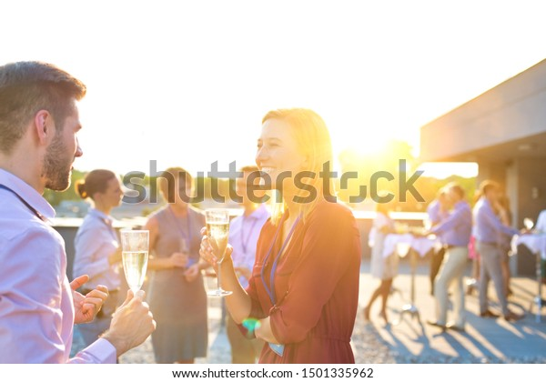 Bsiness people celebrating success at rooftop while drinking champagne with yellow lens flare in background