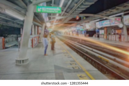 BTS sky train station with unclear background. day time and the train arrive. transportation and connection concept. vintage tone and light effect filter.BTS station, blurred