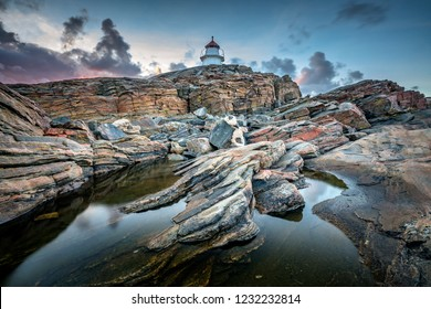 Bua lighthouse and colourfull rocks at sunset