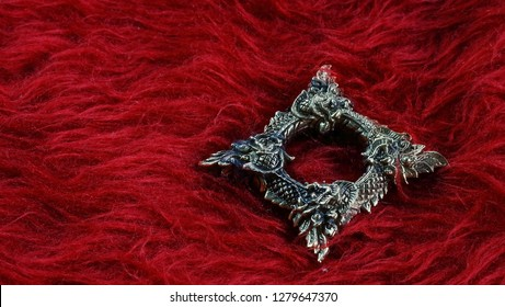 Buang Naka Bas on red background with space for write wording, Thai Naka loop amulet, metal amulet for praying and believe of luck, safety, wealthy and protecting dangerous evil and use for decoration