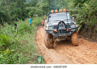 Buayan Penampang Sabah Malaysia - March 13 2017 : Car enthusiast using modified four wheel drive vehicle in rough muddy off road track in Sabah Borneo.