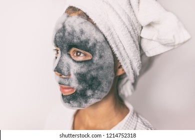 Bubble foam mask woman doing facial beauty treatment with charcoal detox purifying face pores product in home bathroom.