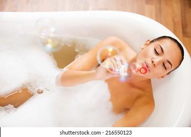 Bubble fun. Top view of beautiful young woman blowing soap bubbles while enjoying bubble bath