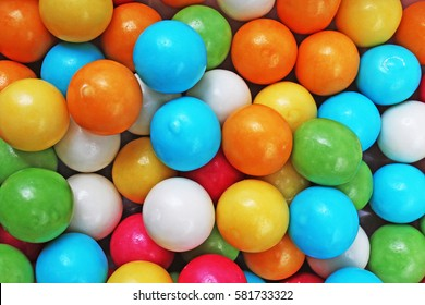 Bubble gum chewing gum texture. Rainbow multicolored gumballs chewing gums as background. Round sugar coated candy bubblegum texture. Food photography. Colorful bubblegums wallpaper.