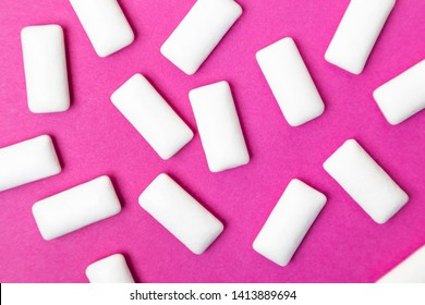 Bubble gum, white dragee on a bright pink background. Stylish photo, minimalism, design, flat lay, top view.