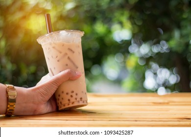Bubble ice milk tea served in takeaway glass with green Bokeh background