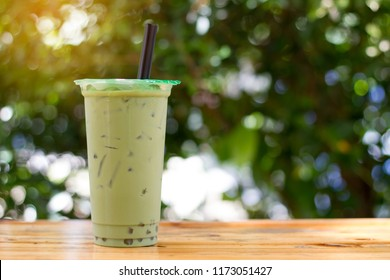 Bubble milk green tea with plastic takeaway glass on the wood table with copy-space for textures and green Bokeh background