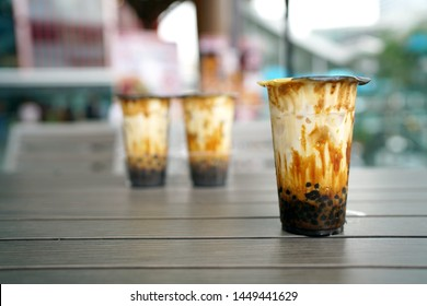 Bubble Milk Tea - Group of  plastic glass of fresh milk with black sugar syrup (Kuromitsu) and hot black pearl (Boba) topped with cream cheese foam on blurred background, Taiwanese style.
