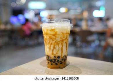Bubble Milk Tea - Holding a plastic glass of fresh milk with salted egg sauce and hot black pearl (Boba) on blurred background, Taiwanese drinking culture.