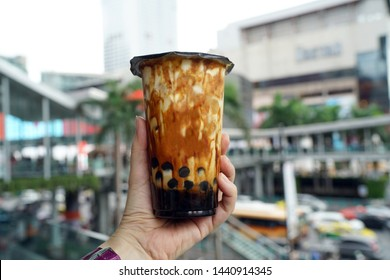 Bubble Milk Tea - Holding a plastic glass of fresh milk with black sugar syrup (Kuromitsu) and hot black pearl (Boba) topped with cream cheese foam on blurred background, Taiwanese style.