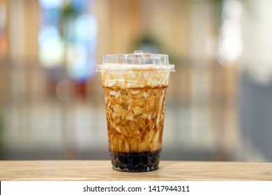 Bubble Milk Tea - A plastic glass of fresh milk with black sugar syrup (Kuromitsu) and hot black pearl (Boba) topped with cream cheese on blurred background, Taiwanese drinking culture.
