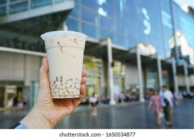 Bubble Milk Tea - A plastic glass of milk tea with brown sugar syrup (Kuromitsu) and hot white pearl (Boba) on blurred background, Taiwanese drinking culture.