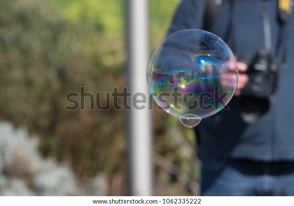 bubble with reflection of trees and water and person with DSLR in background