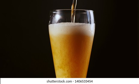 bubbles in the beer in the glass. the beer is poured into a beer glass and it flows in foam in a glass