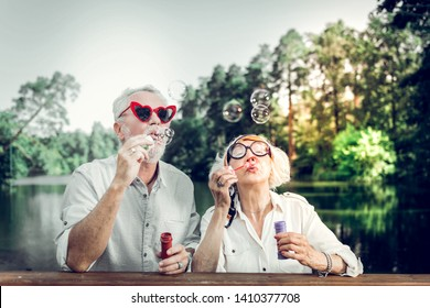Bubbles blowing. Close-up portrait of joyful contended happy charming good-appealing beaming loving caring elderly husband and wife wearing stylish sunglasses having fun while blowing bubbles