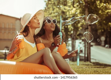 Bubbles blowing. Profile portrait of radiant dark-haired cheerful arresting young ladies in trendy sunglasses and beach clothes blowing the bubbles off outdoors