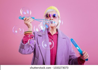 Bubbles time. Elderly lady loving bright colors wearing purple coat while playing with soap bubbles