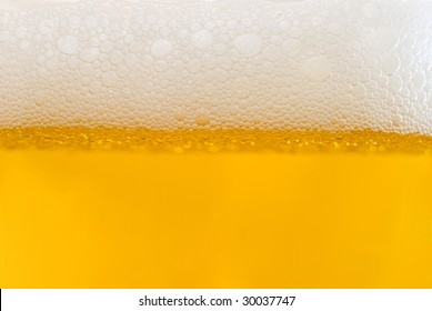 Bubbles of white foam on light beer