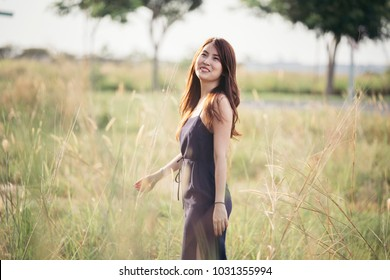 Bubbling lone beautiful young lady smile in tight fitting blue dress and curly long brown hairs stroll and look sideway during morning sun.