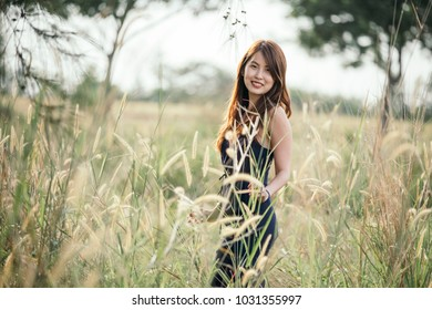 Bubbling lone beautiful young lady smile in tight fitting blue dress and curly long brown hairs stroll dandelion field during morning sun.