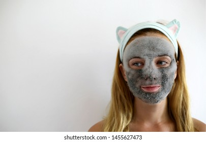 Bubbling mask with charcoal oxygen purifying product on the face of beautiful woman. Skin care mask. Funny headband with ears