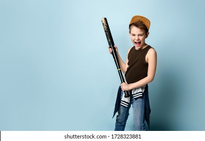 bubby in cap and casual clothes. He is holding black shabby baseball bat or club and screaming, posing against blue studio background. Adolescence and sport concept. Close up, copy space
