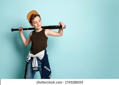 bubby in cap, undershirt, jeans and hoodie tied around his waist. Holding black shabby baseball bat or club, posing on blue background. Childhood, adolescent, aggression. Close up, copy space