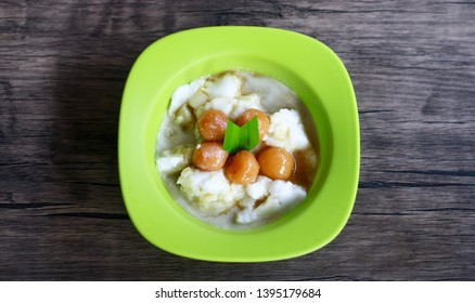 Bubur sum sum on wood background. Bubur sum sum is an Indonesian dessert made by cooking rice flour in coconut milk and served with palm sugar syrup.
