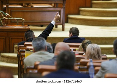 BUCAREST, ROMANIA - JULY 4, 2018: The lider of a parliamentary group signals to his coleagues how to vote during a debate for changing a law, in the Palace of Parliament, on July 4, 2018.