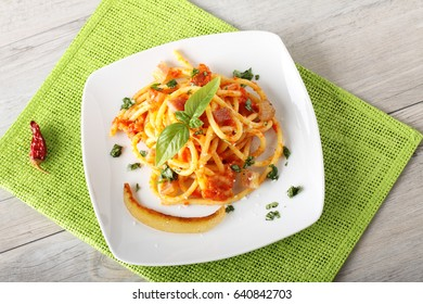 Bucatini Amatriciana, with parmesan cheese, tomato and bacon on complex background