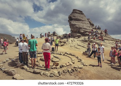 Bucegi Mountains, Romania - August 6, 2016: Tourists participate to a spiritual ritual organized around a spiral of stones near the Sphinx, the sacred megalith located on the Bucegi Mountains plateau.