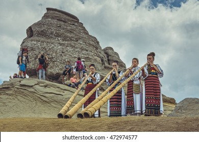 Bucegi Mountains, Romania - August 6, 2016: Young Romanian women dressed in colorful traditional costumes play the tulnic near the Sphinx megalith in Bucegi mountains.