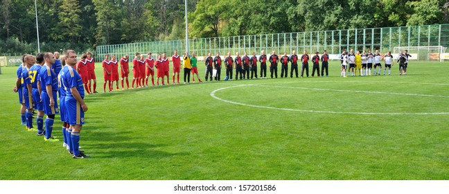 BUCHA, UKRAINE - 23 AUGUST 2013: Amateur football teams of Ukraine and Slovakia listen the hymn before the competition devoted to national Day of Ukrainian flag on August 23, 2013 in Bucha, Ukraine.