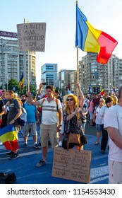 Bucharest, Romania - 10 August 2018: A young couple showing banners at the Diaspora protest against the way Romania is governed by Social Democrats