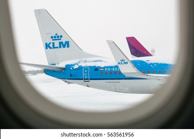 Bucharest, Romania - 11 January 2017: View of a KLM plane through an airplane window waits in the snow to be de-iced at Henri Coanda before take-off. KLM is the oldest airline in the world.