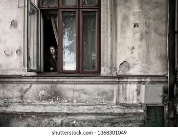 Bucharest, Romania - 4 April 2018: Unidentified women looking out her home apartment window in Bucharest Romania