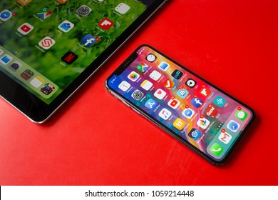 BUCHAREST, ROMANIA - APRIL 1, 2018: Photo of an iphone X and an ipad home screens full of icons on red background