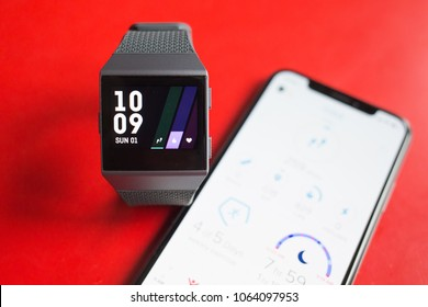 BUCHAREST, ROMANIA - APRIL 1, 2018: photo of an iphone X and a fitbit ionic smartwatch connected wireless via fitbit app