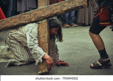 Bucharest, Romania - April 15, 2014: Depiction of exhausted Jesus Christ kneeling under heavy cross during the reenactment of the Way of the Cross.